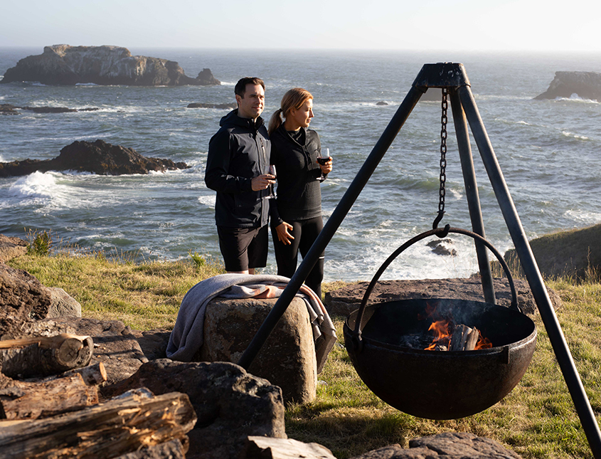 two people drinking wine next to the bluff with a fire pit