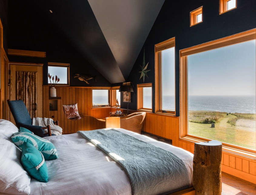 guest bedroom with different shades of blue, dark ceilings, wooden accents and bed facing windows angle view