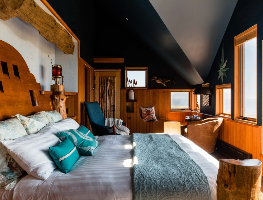 guest bedroom with different shades of blue, dark ceilings, wooden accents and bed facing windows long view