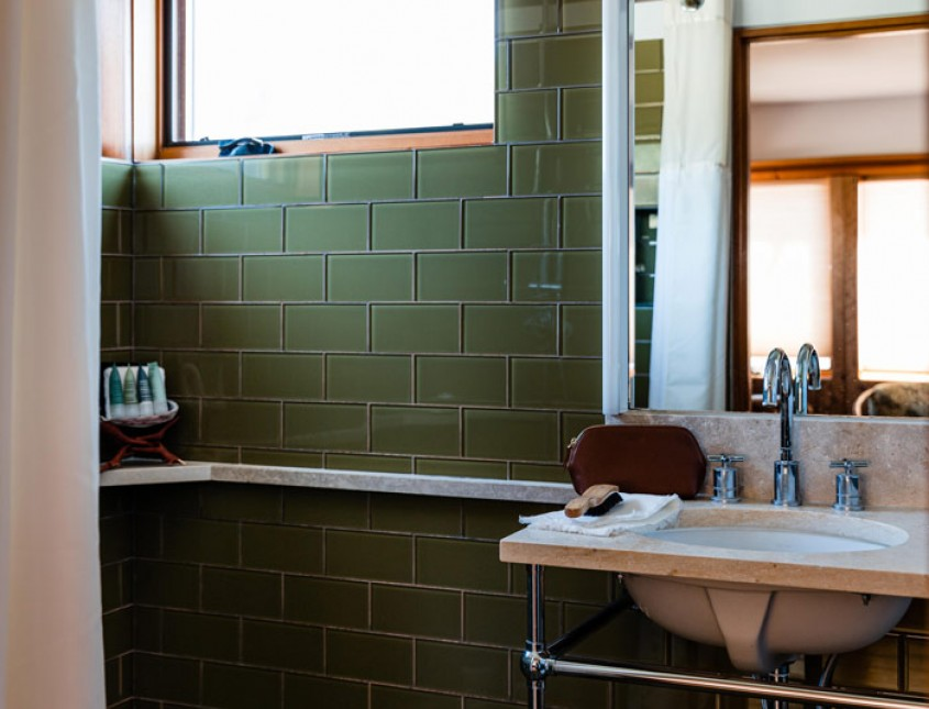 guest bathroom with a shower curtain, green tile, and sink