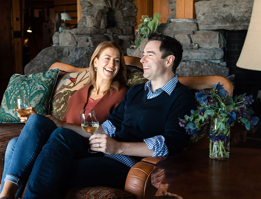 man and woman sitting on a couch drinking wine