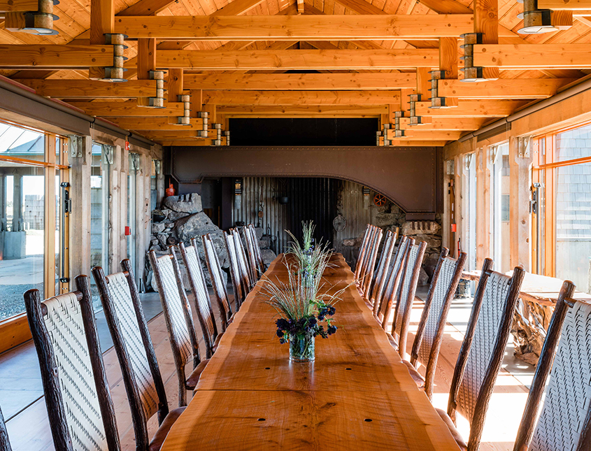 long wood table with green plants and wood beams on ceiling