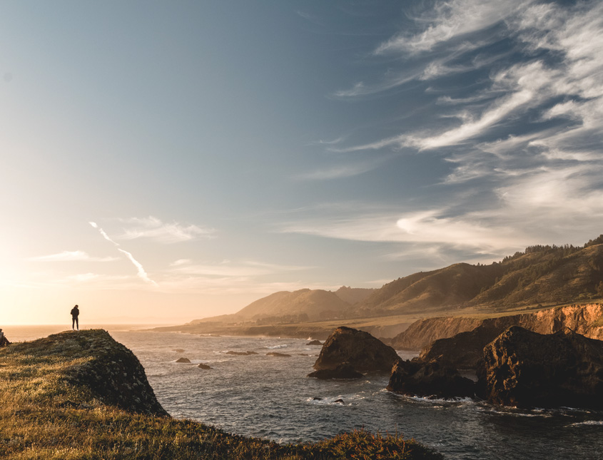 a wide shot of a person in the far distance standing on a cliff overlooking the ocean at sunrise