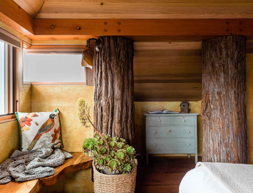 interior of a guest room with two wooden logs built into wall with dresser in between and a wooden bench by window