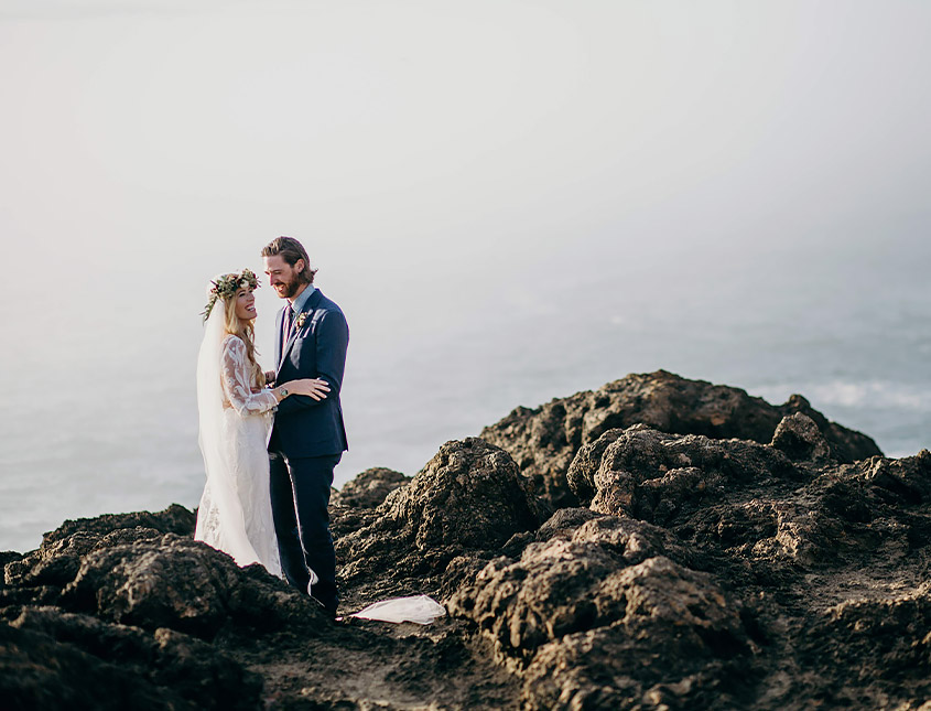 bride and groom standing in between large rocks overlooking the ocean on a cloudy day