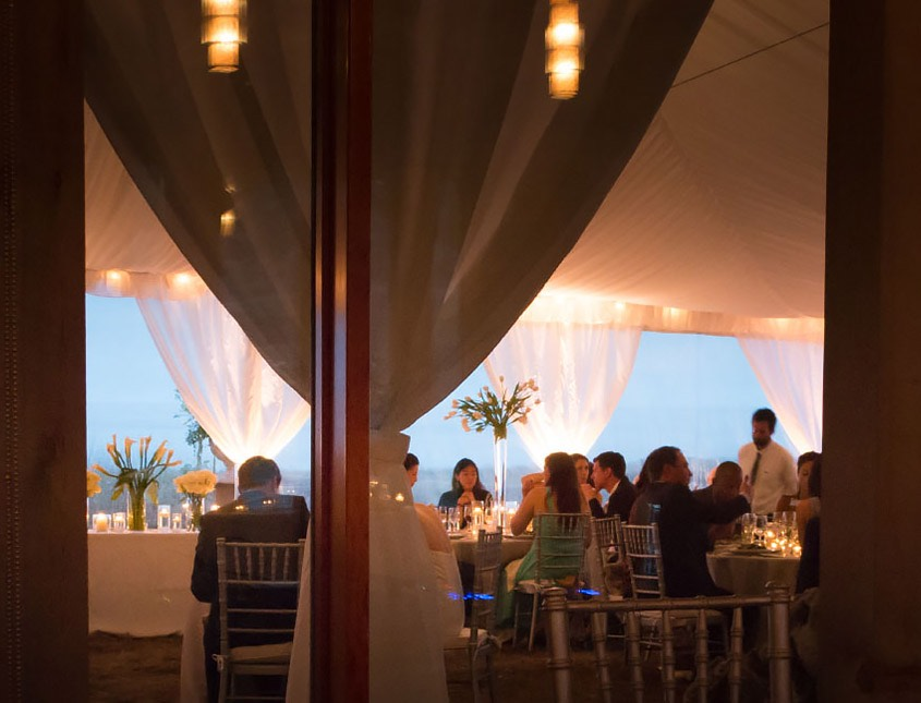 underneath an event tent with formal table seating