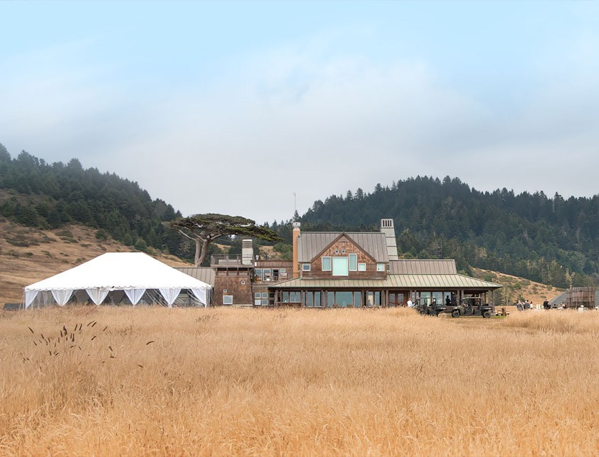 a view of the main inn building and a large white event tent