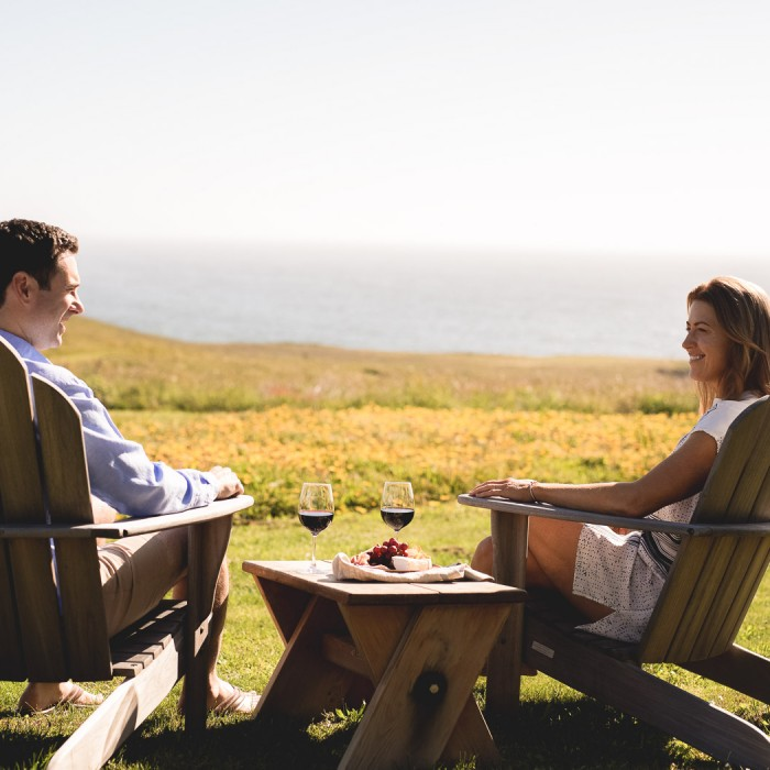 man and woman sitting on patio chairs in the grass drinking wine overlooking the water in the distance