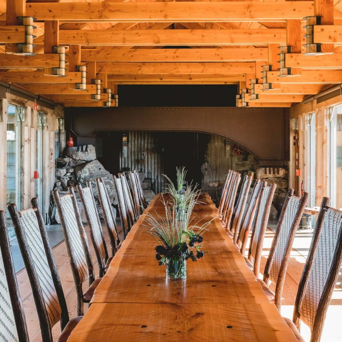 a long wooden dining table with chairs
