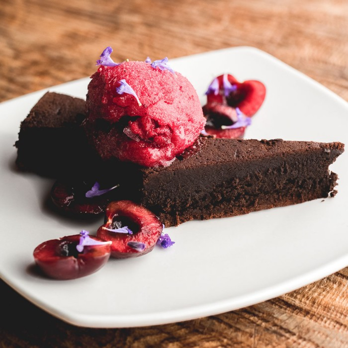 plate of chocolate cake with raspberries and raspberry ice cream on top