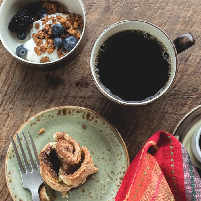 cinnamon roll on a plate, coffee mug, and cup of fruit