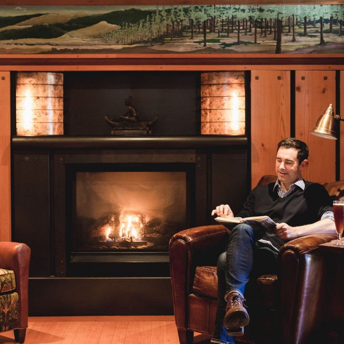 man sitting in a leather chair next to a fireplace reading a book