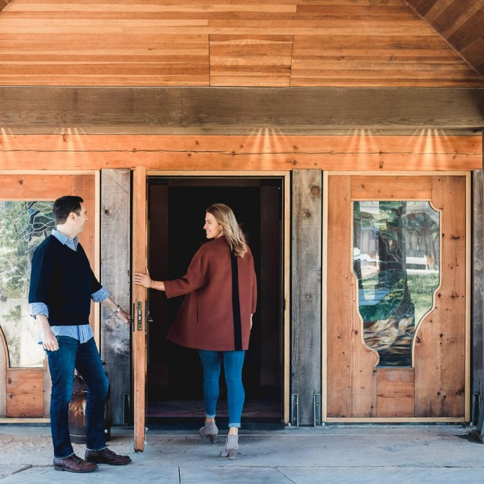 man and woman walking into a wooden building