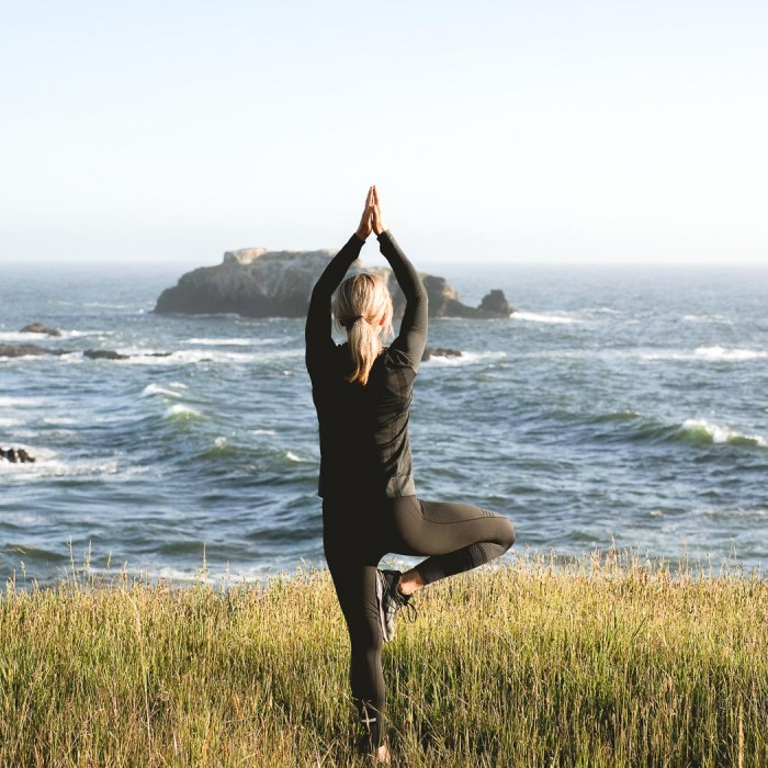 woman doing yoga on grass overlooking the rocky waters