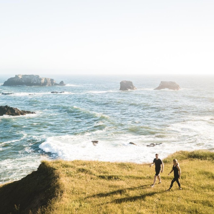 man and woman walking towards the edge of the grassy cliffs to look at the ocean water
