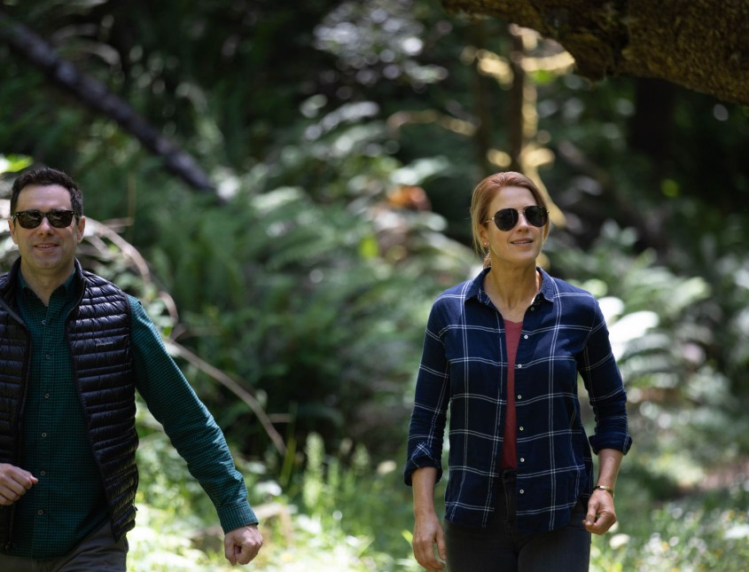 middle aged couple walking through the forest