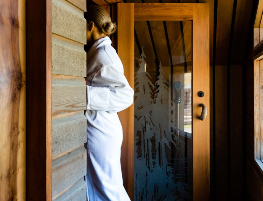 woman in a white bath robe walking into a door