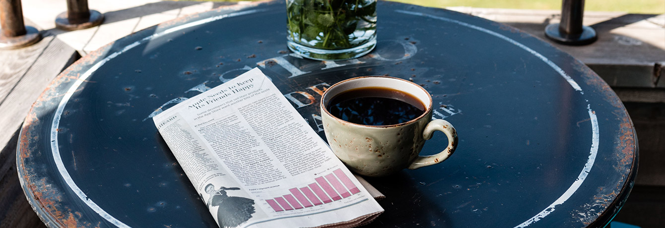 coffee mug and paper on a patio table