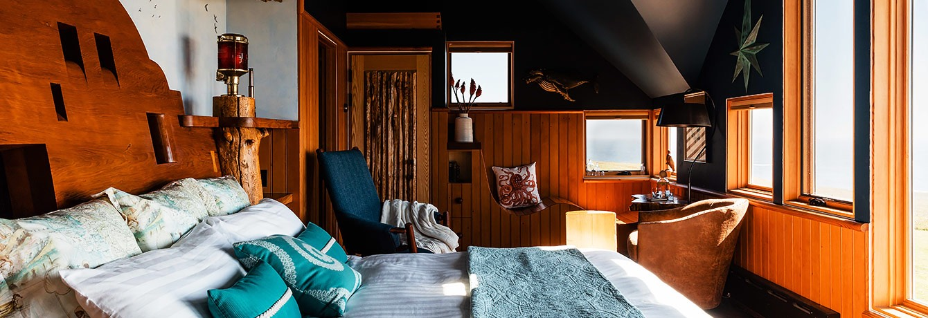 guest bedroom with different shades of blue, dark ceilings, wooden accents and bed facing windows close up of bed