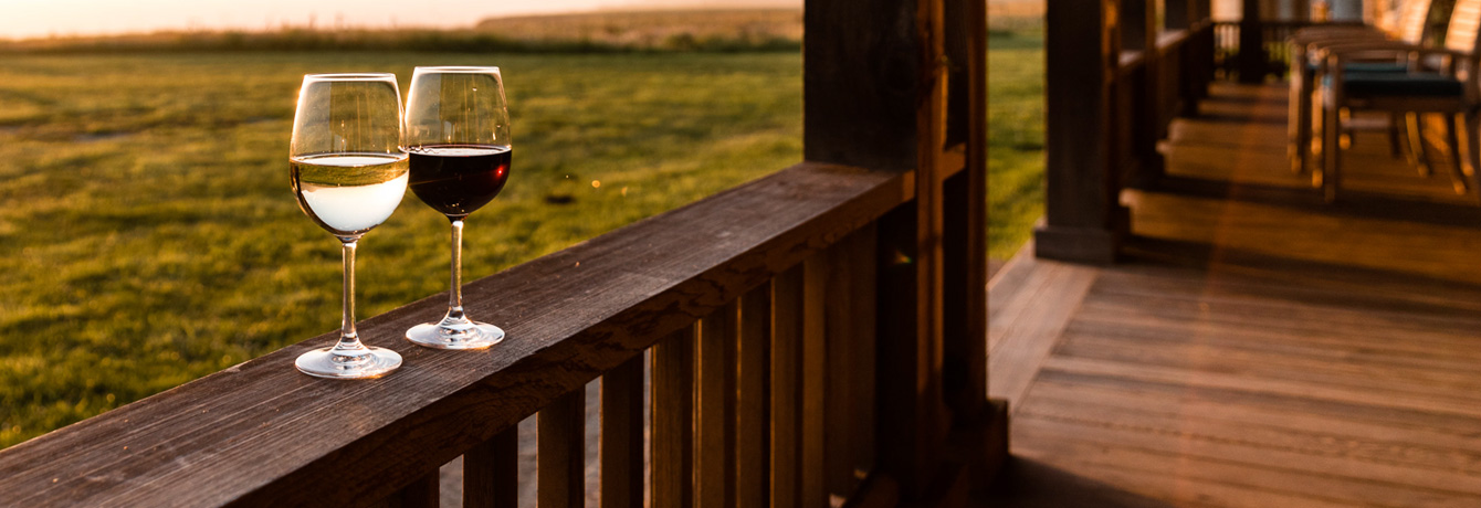 two glasses of wine sitting on a wooden porch railing