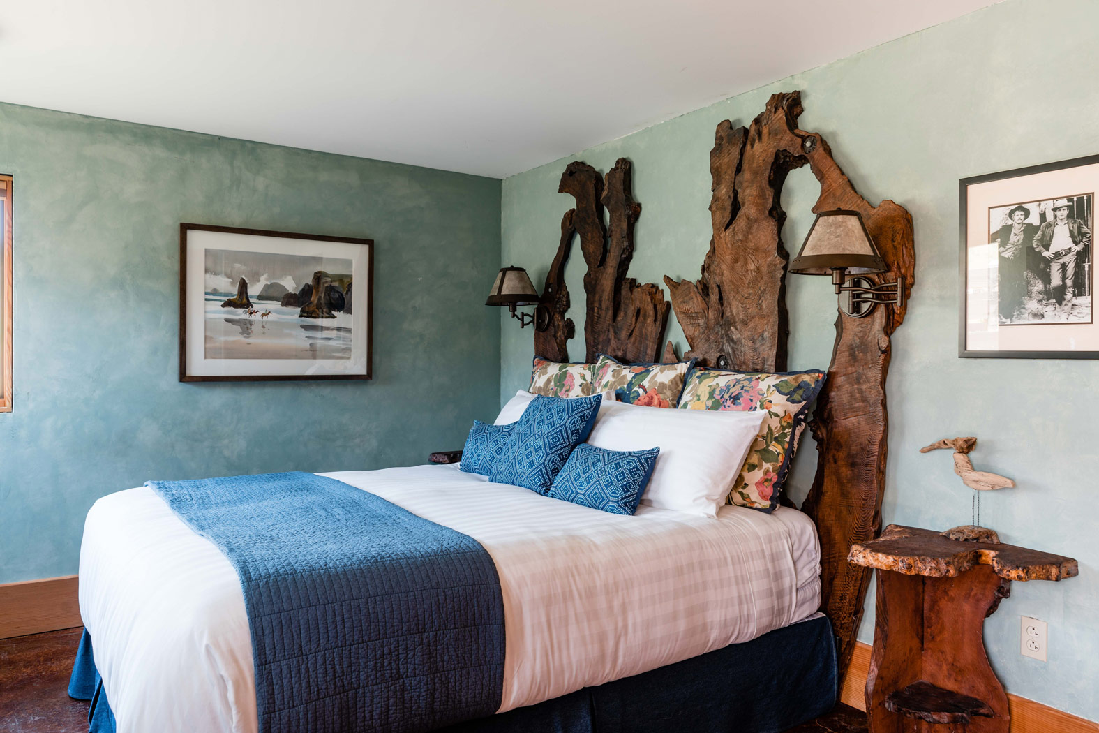 guest room with white linens, navy pillows and blankets, and a wooden headboard