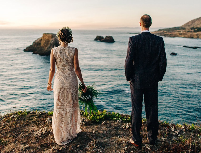 bride and groom standing on rocks overlooking the ocean