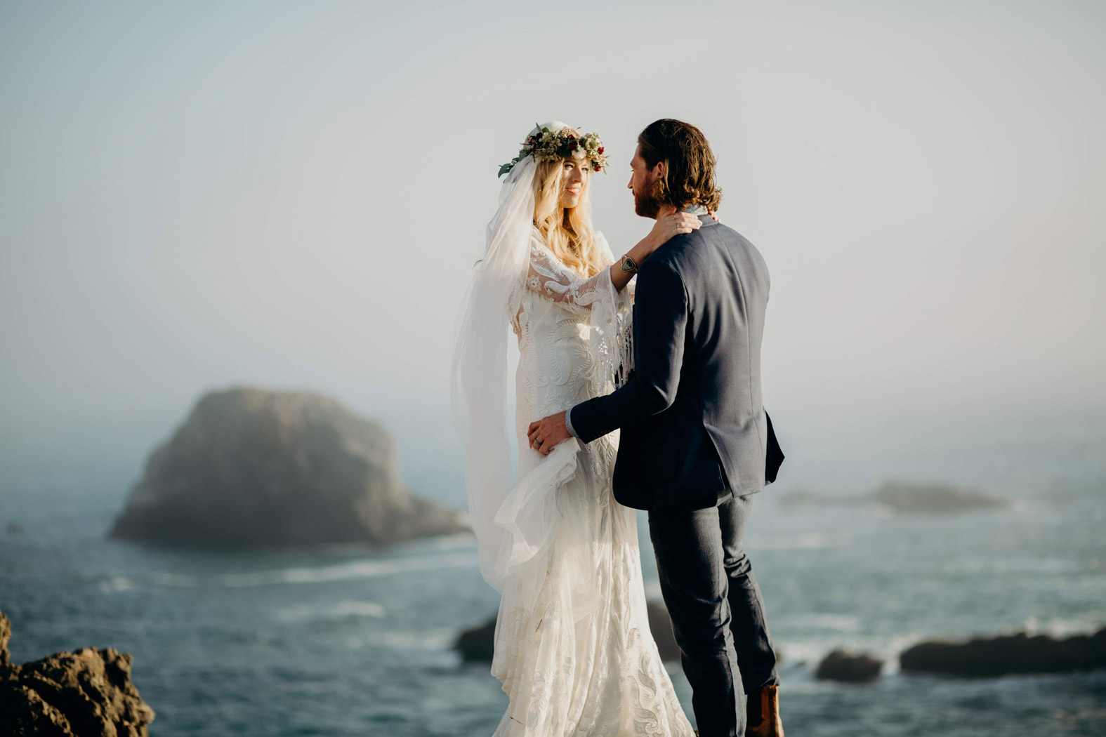 bride and groom with their arms around each other and ocean in distance