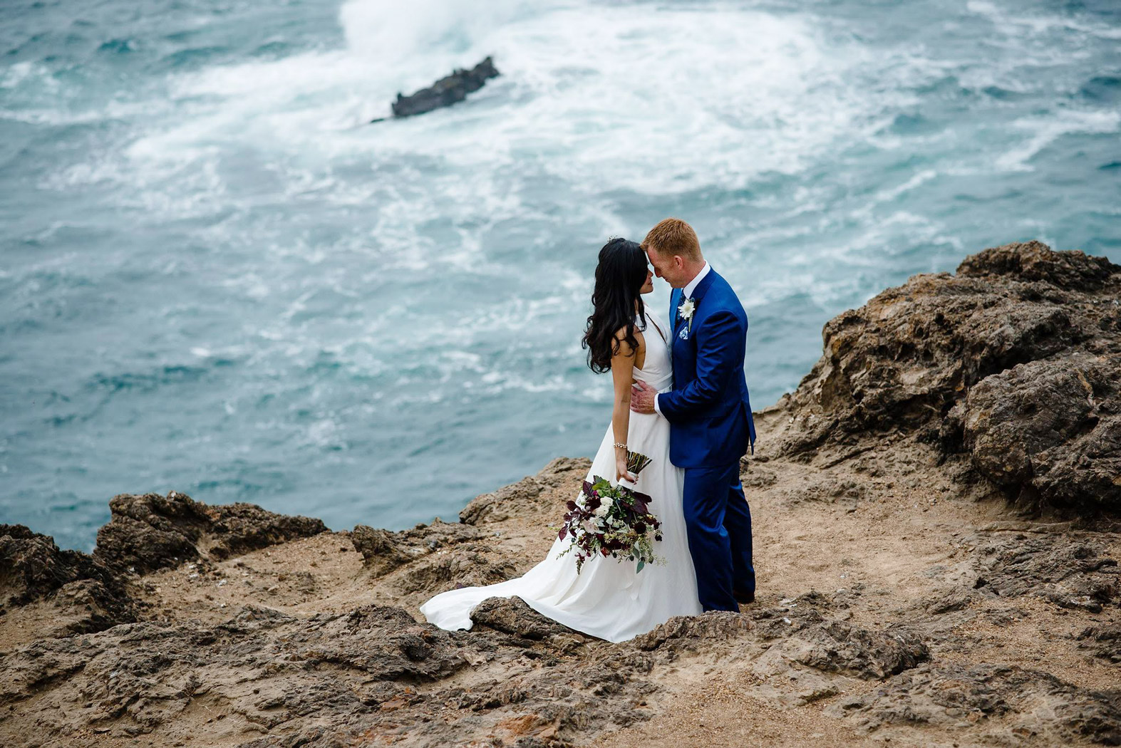 bride andgroom standing on the edge of a cliff overlooking the ocean water