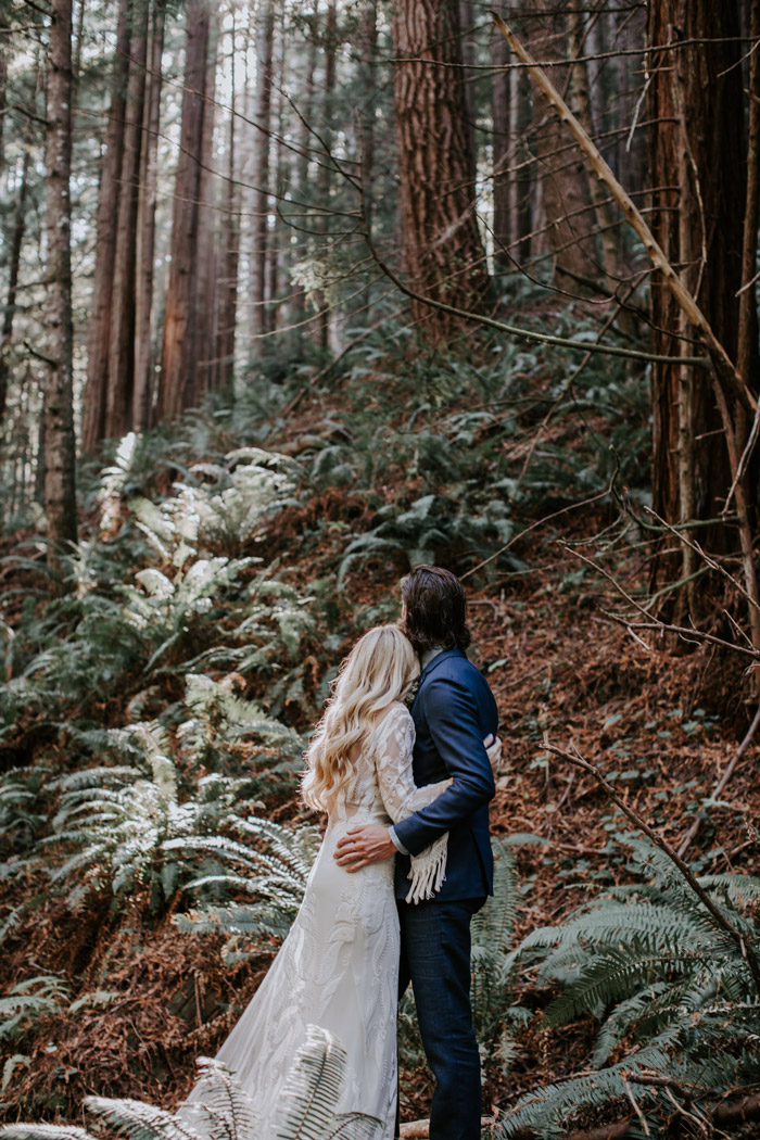 bride and groom hugging looking towards the trees in a forest