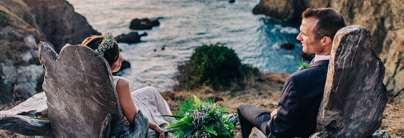 bride and groom sitting on wooden lawn chairs overlooking the ocean from the cliffs