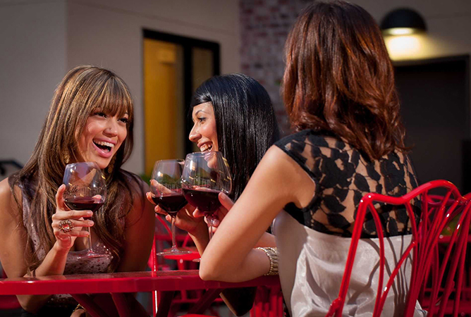 women drinking wine and laughing