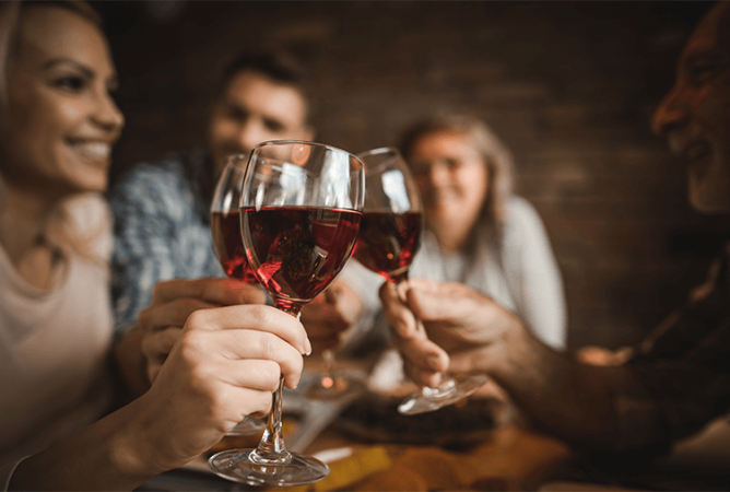 group of friends clinking wine glasses together