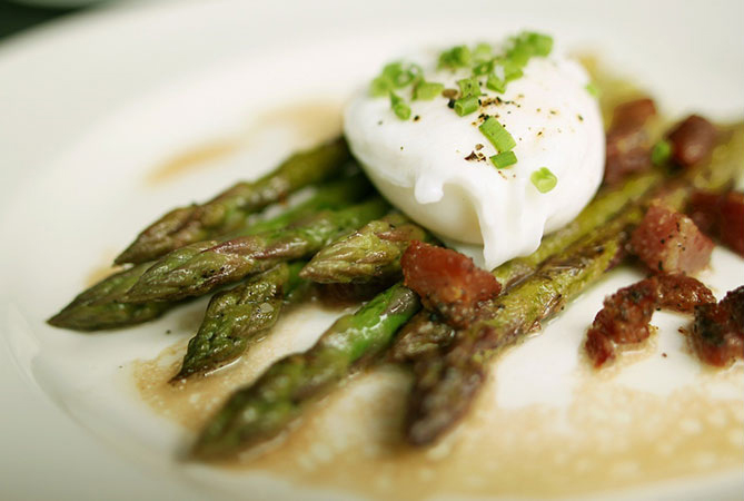 asparagus on white plate with poached egg on top