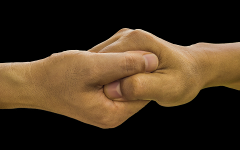 Closeup on hands clasped together in gesture of solidarity between two persons