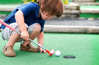 Little boy playing mini golf