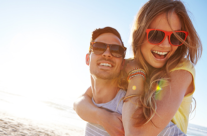 Cheerful couple on beach with sunglasses