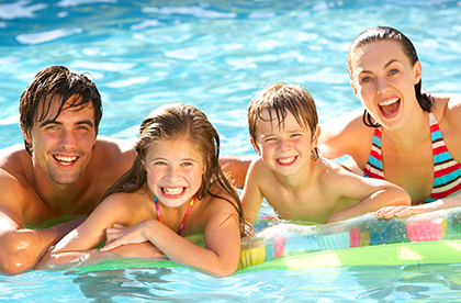 Cheerful family of four smiling on a water floaty