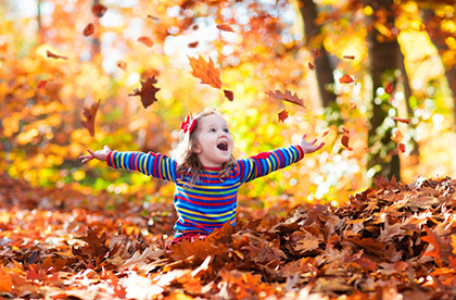 Child playing in fall leaves