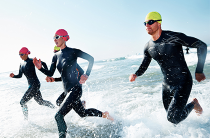 Four people in dive suits and swimming head gear running on the shore of the ocean