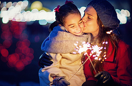 Mother and daughter in sweaters at night with sparkler in hand