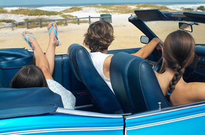 Friends driving in a blue convertible near the beach