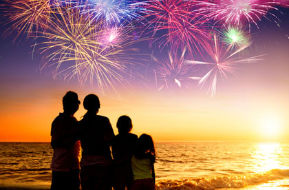 Happy family enjoying the sunset and fireworks on the beach