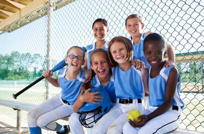 Youth softball girls laughing while sitting on bench