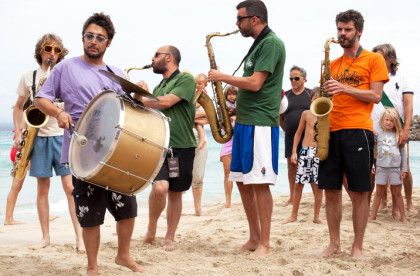 a casual band with a series of instruments performing on the beach