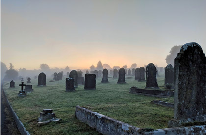 a graveyard during the sunset that looks spooky with fog