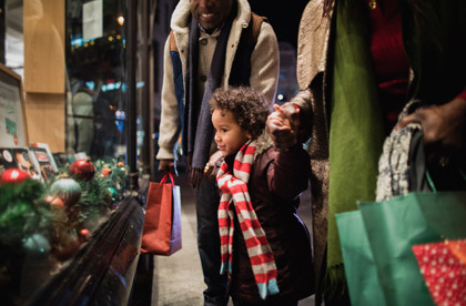 little boy looking in a window while shopping with his parents during christmas