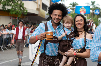 a family smiling and in the street during the Oktoberfest celebration, dressed up in German outfits and drinking beer