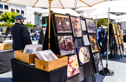 an art festival with a man in his own section showcasing his art to the public outside