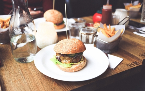 Burger dishes and side of fries with glasses of water