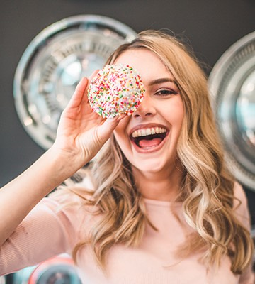 a woman holding a sprinkled donut in front of her eye and smiling